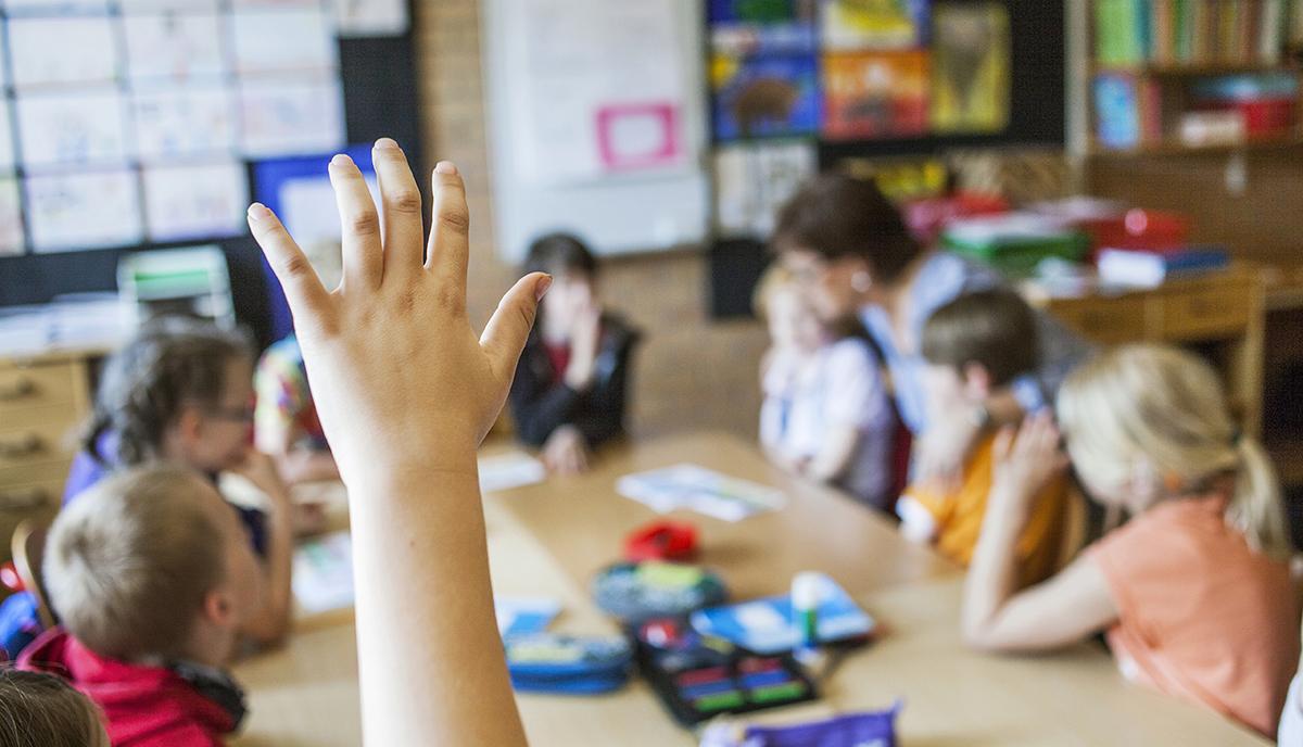 En uppsträckt  hand i ett klassrum
