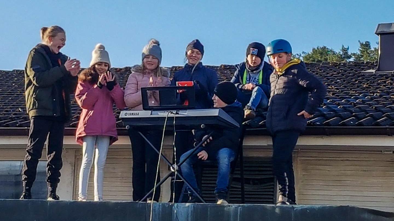 Elever med piano på skolans tak